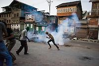Srinagar, India-August 9, 2010: A Kashmiri protester tries to extinguish a tear-gas canister in downtown Srinagar