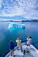 Tourist and floating glacier iceberg, altocumulous clouds, Prince William Sound, Alaska