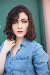 Vintage style woman with curly brunette hair wearing denim shirt