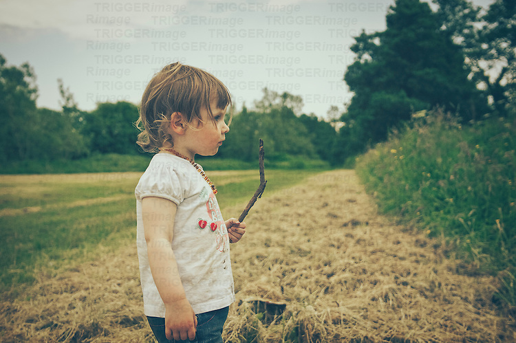 A girl playing with a stick in a field