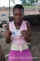 Africa, Swaziland, Malkerns. Women selling corn in the local Manzini market. This girl carries a picture of the father she doesn't know.