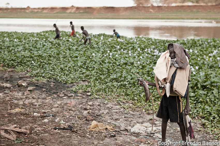 Portrait of a boy holding fish and his friends clothing while they hunt catfish with spears in the background. Sobat River, Nasir, South Sudan.