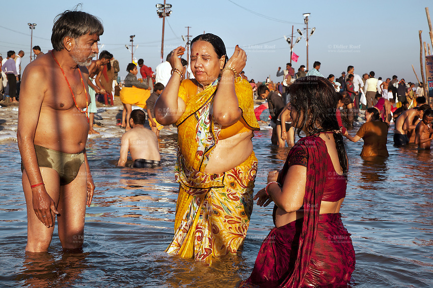 India. Uttar Pradesh state. Allahabad. Maha Kumbh Mela. An Indian Hindu devotee family takes a holy dip  in Sangam. Mother and daughter wear sarees while father has his. The Kumbh Mela, believed to be the largest religious gathering is held every 12 years on the banks of the 'Sangam'- the confluence of the holy rivers Ganga, Yamuna and the mythical Saraswati. In 2013, it is estimated that nearly 80 million devotees took a bath in the water of the holy river Ganges. The belief is that bathing and taking a holy dip will wash and free one from all the past sins, get salvation and paves the way for Moksha (meaning liberation from the cycle of Life, Death and Rebirth). Bathing in the holy waters of Ganga is believed to be most auspicious at the time of Kumbh Mela, because the water is charged with positive healing effects and enhanced with electromagnetic radiations of the Sun, Moon and Jupiter. The Maha (great) Kumbh Mela, which comes after 12 Purna Kumbh Mela, or 144 years, is always held at Allahabad. Uttar Pradesh (abbreviated U.P.) is a state located in northern India. 7.02.13 © 2013 Didier Ruef