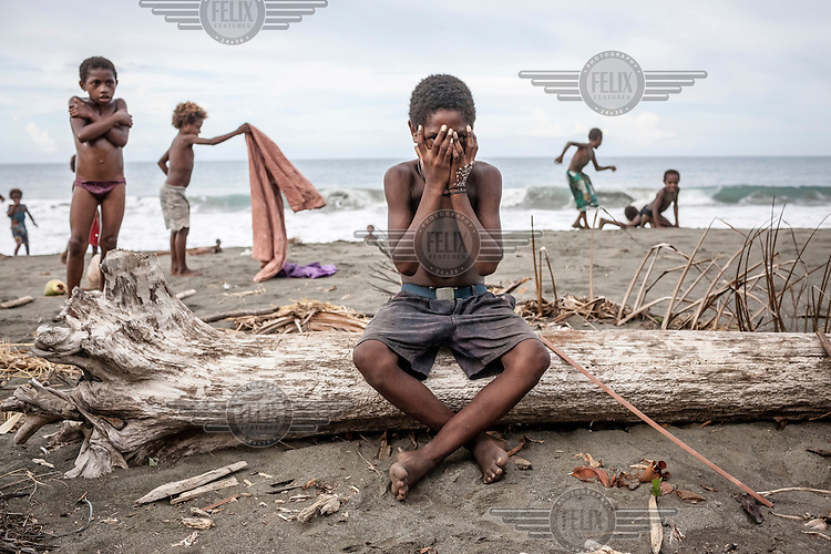 Nobert Mor, 13, sits on a dead tree trunk surrounded by children playing on the sea shore.