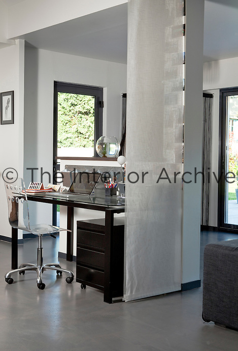 An office space is situated adjacent to the front door and is screened from the living area by a long curtain