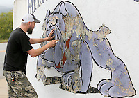 NWA Democrat-Gazette/DAVID GOTTSCHALK  Jeff Jackson, art teacher at Fayetteville High School, scrapes paint Wednesday, September 30, 2015 as he prepares the Fayetteville High School Bulldog Mural on the corner of College Avenue and Rock Street. The mural will be repainted by Fayetteville High School National Art Honor Society students who will receive community service credit for their work.