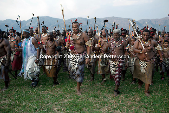 LUDZIDZINI, SWAZILAND - AUGUST 30: King Mswati III dances in front of young virgins at a traditional Reed dance ceremony at the stadium at the Royal Palace on August 30, 2009, in Ludzidzini, Swaziland. About 80.000 virgins from all over the country attended this yearly event, the biggest in Swazi culture. It was founded to celebrate the beauty of Swazi women and girls. King Mswati III, and absolute monarch, was born in 1968 and he has 14 wives and many children. The king danced with his men in front of the 80.000 girls. Many of the girls hope to get noticed by the king and to be chosen as a future wife, a ticket from poverty and into a life of privilege and luxury. The country is one of the poorest in the world and it is struggling with a high prevalence of HIV-Aids and severe poverty. (Photo by: Per-Anders Pettersson)...