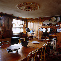 The basement dining room has an old-fashioned stove and walls decorated with fretwork