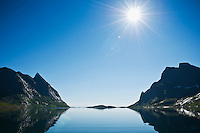 Summer sun shines over Kjerkfjord, Reine, Lofoten islands, Norway