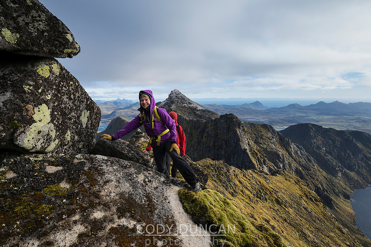Female hikers climb steep rocky ridge towards Østhimmeltind mountain peak, Vestvågøy, Lofoten Islands, Norway