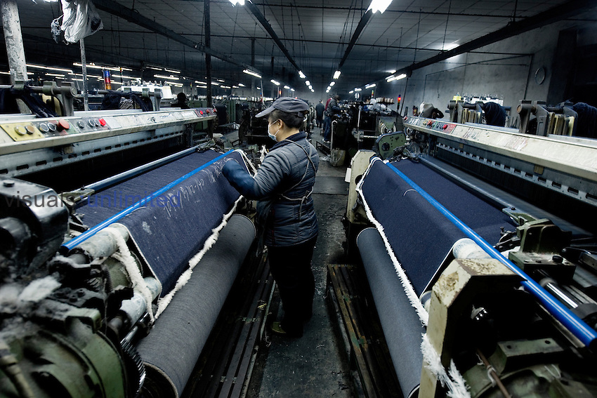 Worker at a power loom weaving denim for blue jeans in a textile company, LSH, Xintang, Guangdong Province, China