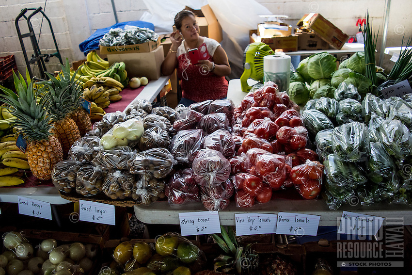 A local produce vendor inserts the ear bud for her smartphone into her ear at the Hilo Farmers Market, Big Island of Hawai'i.