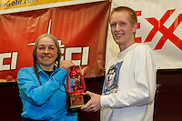 Wells Fargo, Tyler Hull, presents Marcelle Fresineau with the Red Lantern Award at the musher 's finishers banquet in Nome on Sunday March 16 after the 2014 Iditarod Sled Dog Race.<br /> <br /> PHOTO (c) BY JEFF SCHULTZ/IditarodPhotos.com -- REPRODUCTION PROHIBITED WITHOUT PERMISSION