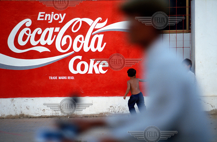 Children play in front of a Coca-Cola advert painted on a city wall.