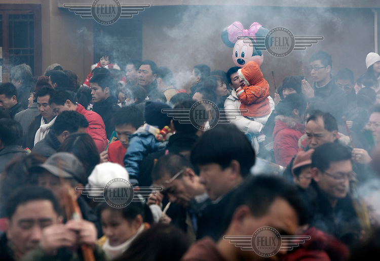 Worshippers, holding large sticks of burning insense and, in one case, a Disneyesque giant mouse balloon, crowd into Longhua Temple to pray on the first day of the Year of the Ox.
