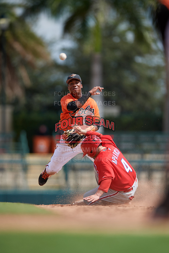 Baltimore Orioles Jean Carmona (52) throws to first base to try to complete a double play as Juan Aparicio (4) slides into second base during a Florida Instructional League game against the Philadelphia Phillies on October 4, 2018 at Ed Smith Stadium in Sarasota, Florida.  (Mike Janes/Four Seam Images)