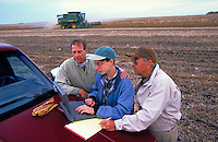 Three generation family of farmers use latest technology with laptop computer in the field during harvest.