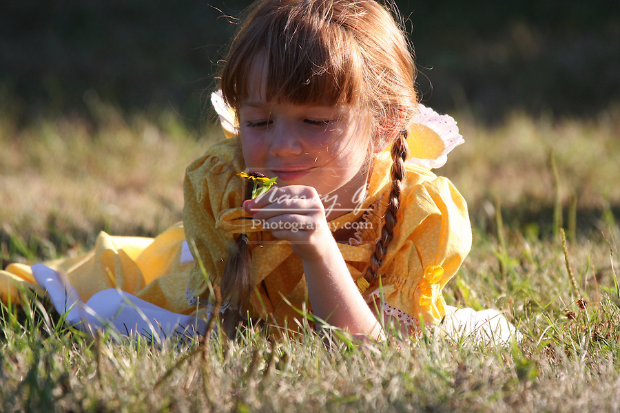A young girl holding a daisy flower