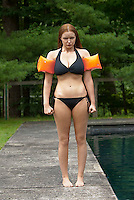Woman wearing water wings, looking at camera, pouting