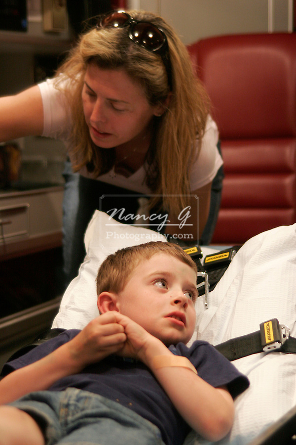 A concerned mother and hurt child inside an ambulance