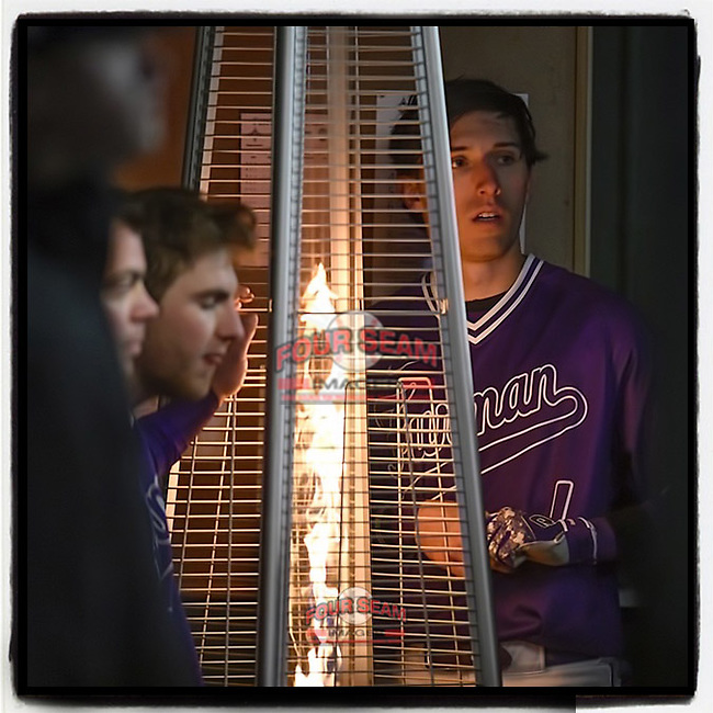 Furman Paladins players, including Banks Griffith, right, warm up by a space heater in the dugout in a 37-degree game against the Clemson Tigers on Tuesday, March 5, 2019, at Fluor Field at the West End in Greenville, South Carolina. Clemson won, 3-1. (Tom Priddy/Four Seam Images)