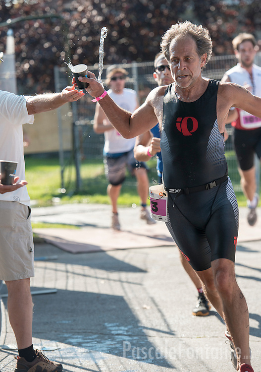 A runner squishes most his water from the glass he grabbed.
