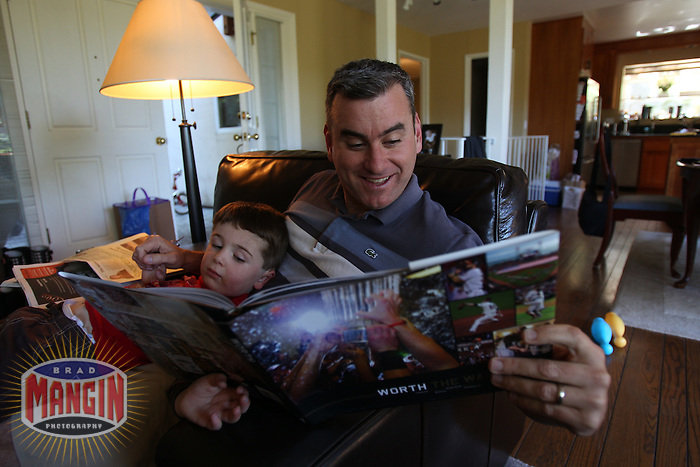"OAKLAND, CA - MARCH 30:  Author Brian Murphy and son Declan Murphy look at the new book about the San Francisco Giants 2010 World Series season entitled ""Worth The Wait"" for the first time in their home on March 30, 2011 in Oakland, California. Photo by Brad Mangin"