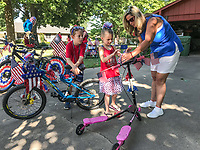 NWA Democrat-Gazette/SPENCER TIREY Lori Pierce (right) helps Anneli Evans (6) decorate her bike with Wyatt Evans (9) before participating in a 4th of July parade in the Turtle Creek Place subdivision in Rogers. The parade was organized by Camryn Hodge an 8-year-old who wanted to show how much she loved America and wanted to make new friends in the neighborhood.