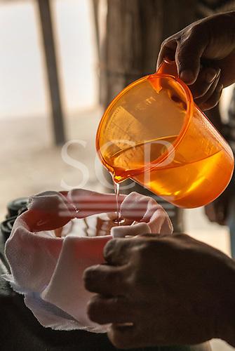 Aldeia Baú, Para State, Brazil. Filtering babassu nut oil through a cloth filter using a clean orange plastic measuring jug.