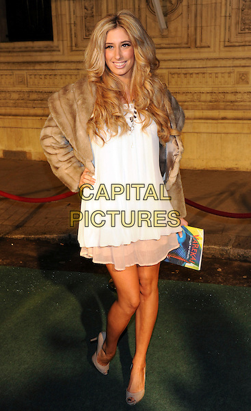 STACEY SOLOMON.Arrivals at Cirque du Soleil's Varekai gala opening night at the Royal Albert Hall, London, England. .January 5th, 2009 .full length white layered layers dress brown cropped fur jacket hand on hip tanned bare legs sun tan beige peep toe grey gray shoes .CAP/CJ.©Chris Joseph/Capital Pictures.