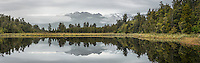 Southern Alps and rainforest reflecting in Lake Matheson on cloudy, rainy day, Westland Tai Poutini National Park, UNESCO World Heritage Area, West Coast, New Zealand, NZ