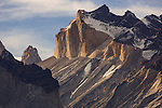 Sunset light illuminates the yellow granite face of Monte Almirante Nieto.  To the left is the tip of Torre Central or Central Tower of the Torres del Paine.  Torres del Paine National Park in Patagonia, Chile.  A UNESCO World Biosphere Reserve.