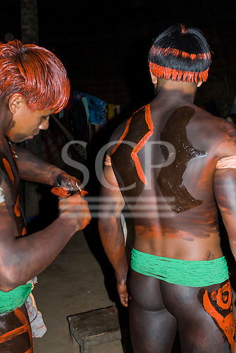 Xingu Indigenous Park, Mato Grosso State, Brazil. Aldeia Afukuri (Kuikuro). Young men preparing for the festival of Taquara; body paint.