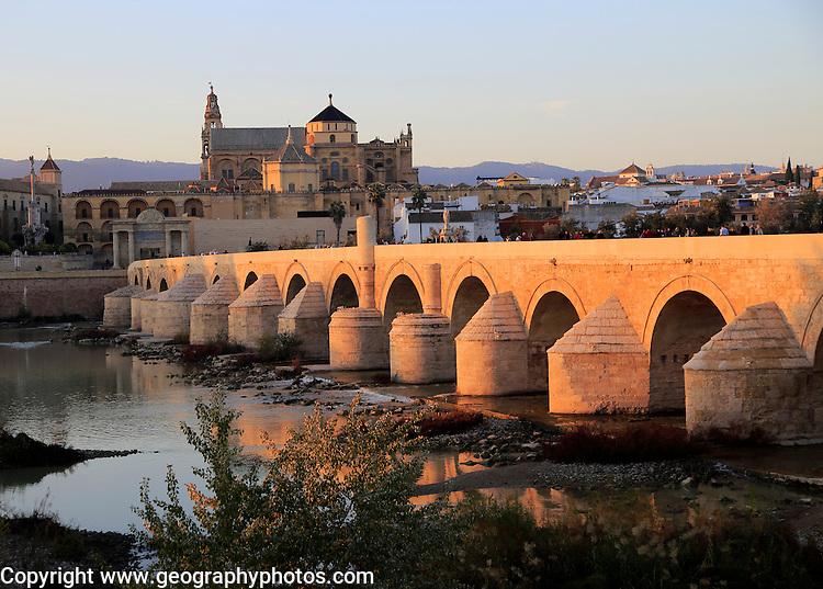 Roman bridge spanning river Rio Guadalquivir with Mezquita cathedral buildings, Cordoba, Spain