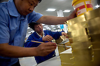 "Amity Printing Company employees place and glue bookmark ribbons into newly-bound Bibles in the Amity Printing Company's new printing facility in Nanjing, China...On May 18, 2008, the Amity Printing Company in Nanjing, Jiangsu Province, China, inaugurated its new printing facility in southern Nanjing.  The facility doubles the printing capacity of the company, now up to 12 million Bibles produced in a year, making Amity Printing Company the largest producer of Bibles in the world.  The company, in cooperation with the international organization the United Bible Societies, produces Bibles for both domestic Chinese use and international distribution.  The company's Bibles are printed in Chinese and many other languages.  Within China, the Bibles are distributed both to registered and unregistered Christians who worship in illegal ""house churches."""