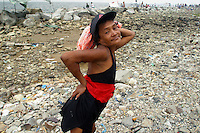 """Aling Remy, aka """"Kokwang"""", strikes a pose for the camera while taking a break from bathing at a rocky stretch of shore by the GSIS compound in Pasay City. She along with hundreds other Metro Manila residents who cannot afford a trip to the provinces made do with the modest and sometimes trashy beaches of Manila Bay on Black Saturday. 26 march 2005"""