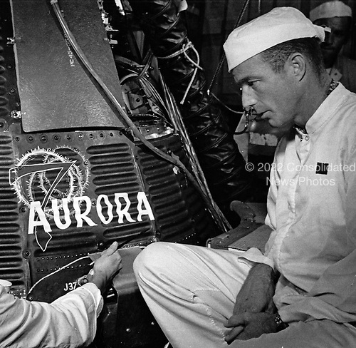 Mission pilot M. Scott Carpenter looks on as Cecelia Bibby, an employee of the Chrysler Corporation (not pictured) paints the name &quot;Aurora 7&quot; on a Project Mercury spacecraft for the United States' second manned orbital flight, at Cape Canaveral, Florida on May 19, 1962.<br /> Credit: NASA via CNP