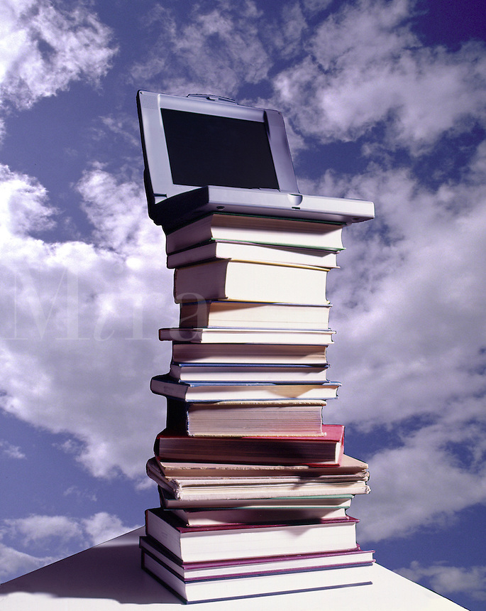 Laptop computer sitting on a pile of books against a sky background, knowledge, old and new.