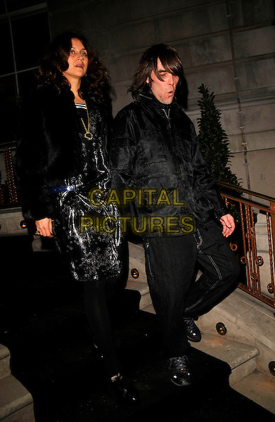 IAN BROWN & GUEST.The Dom Perignon Vintage Champagne party, The Landau restaurant, London, England..February 26th, 2008.full length black dress jacket jeans denim .CAP/CAN.©Can Nguyen/Capital Pictures.