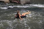 Woman floating in inner tube at Boulder Creek, Boulder, Colorado. .  John offers private photo tours in Denver, Boulder and throughout Colorado. Year-round.