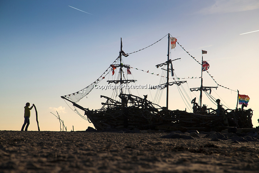 28/11/16<br /> <br /> As the cold front sweeps in with blue skies and freezing temperatures, a walker admires the Black Pearl pirate ship, made completely out of driftwood, on New Brighton beach with the Liverpool skyline and Royal Liver building in the background. The boat was built in 2013 by local artist Frank Lund and his friend Major Mace using materials found on their beach walks. The work of art has survived numerous storms and being set alight by vandals and is now a popular spot for tourists and locals alike. There was even a pirate wedding held on its deck last year.<br /> <br /> All Rights Reserved F Stop Press Ltd. (0)1773 550665   www.fstoppress.com