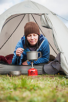 Female backpacker cooks from entrance of tent