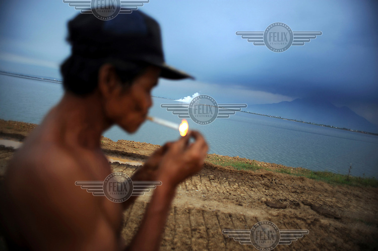 A man lights a cigarette standing on the dam overlooking the area where his village and rice fields lie submerged. Since May 2006, more than 10,000 people in the Porong subdistrict of Sidoarjo have been displaced by hot mud flowing from a natural gas well that was being drilled by the oil company Lapindo Brantas. The torrent of mud - up to 125,000 cubic metres per day - continued to flow three years later.