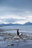 ALASKA, Homer, kids play by the edge of Kachemak Bay at Bishop Beach with the Kenai Mountains in the distance