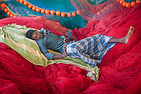 An Indian fisherman takes an afternoon nap among his nets in the Southern Indian state of Tamil Nadu, India on the 1st of November 2010.