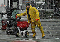 Snow falls as a man spreads salt  in Jersey City during the season's first snow storm on December 10, 2013 in New York City Photo by Kena Betancur / VIEWpress.
