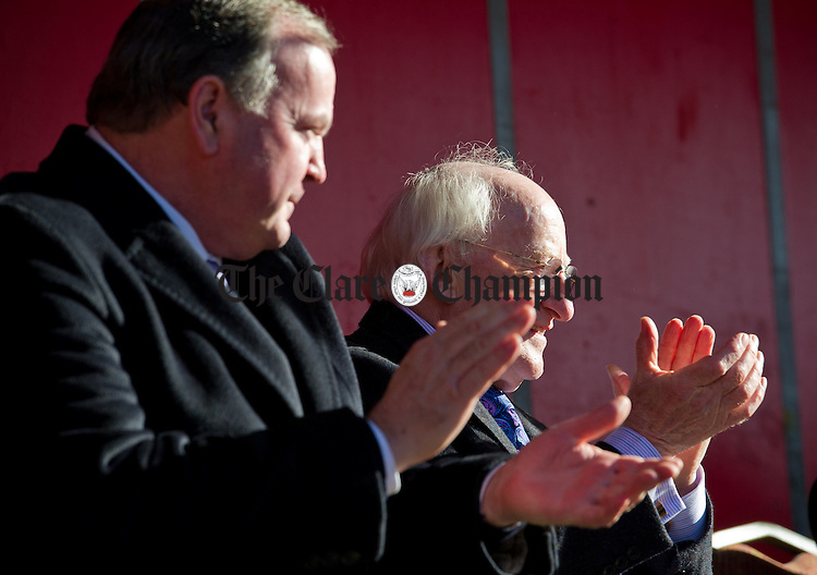 President Michael D. Higgins and GAA president Liam O Neill watch the parade file through Ennis to Cusack Park for the Ireland V Scotland senior hurling shinty International game, to mark the official opening of Fr Mc Namara Memorial Park in Doora. Photograph by John Kelly.