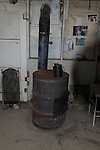 Old barrel used as stove and heater in miner's shack