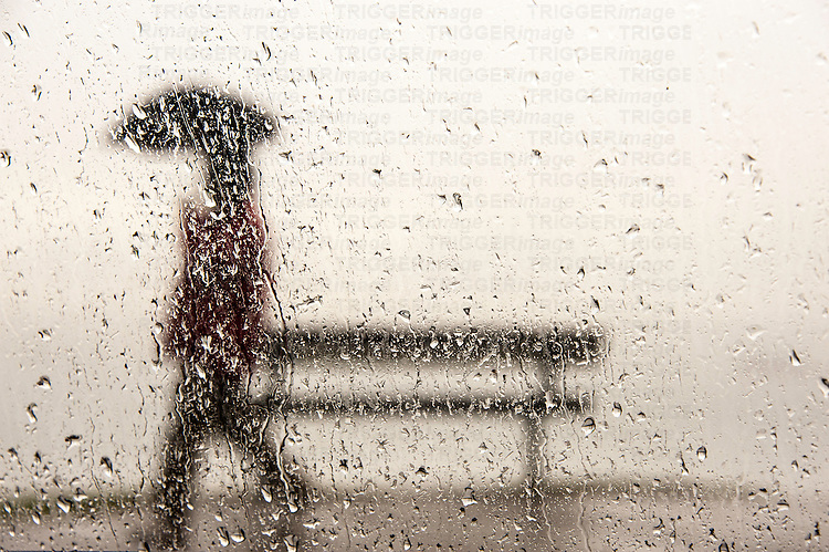 A man walking with an umbrella against a rain streaked window
