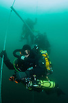 Divers decompress from a deep trimix technical dive. The ropes are part of a decompression station which detaches from the main shot line and drifts in the current making long decompression times more comfortable. It also ensures the team all return to a single point which is safer in case of problems.
